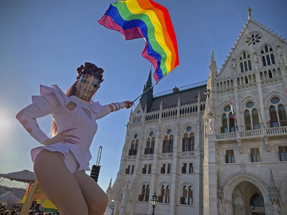 In this file photo dated June. 14, 2021, a drag queen waves a rainbow flag during an LGBT rights demonstration in front of the Hungarian Parliament building in Budapest, Hungary.