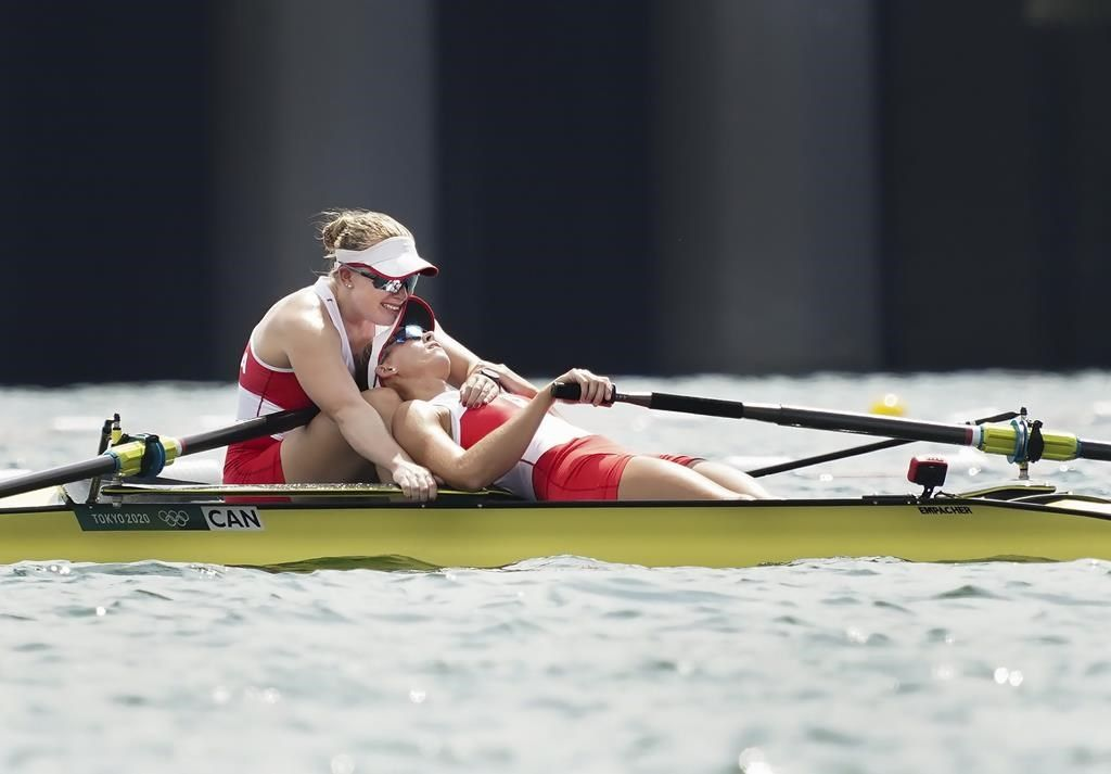 An exhausted Hillary Janssens collapses backward into the arms of an equally spent Caileigh Filmer after the Canadian duo won the bronze in the women's pair rowing final event during the Tokyo Summer Olympic Games on Thursday, July 29, 2021. THE CANADIAN PRESS/Nathan Denette.