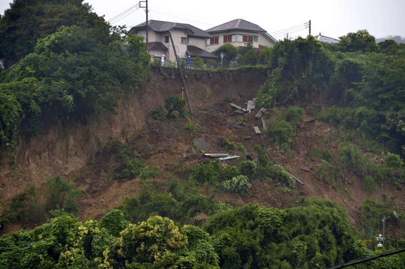 First responders observe a landslide caused by heavy rains in Zushi, Kanagawa prefecture, west of Tokyo on Saturday, July 3, 2021. In Atami in Shizuoka prefecture, authorities in Japan say multiple people are missing after a powerful mudslide swept away rows of houses.(Kyodo News via AP).