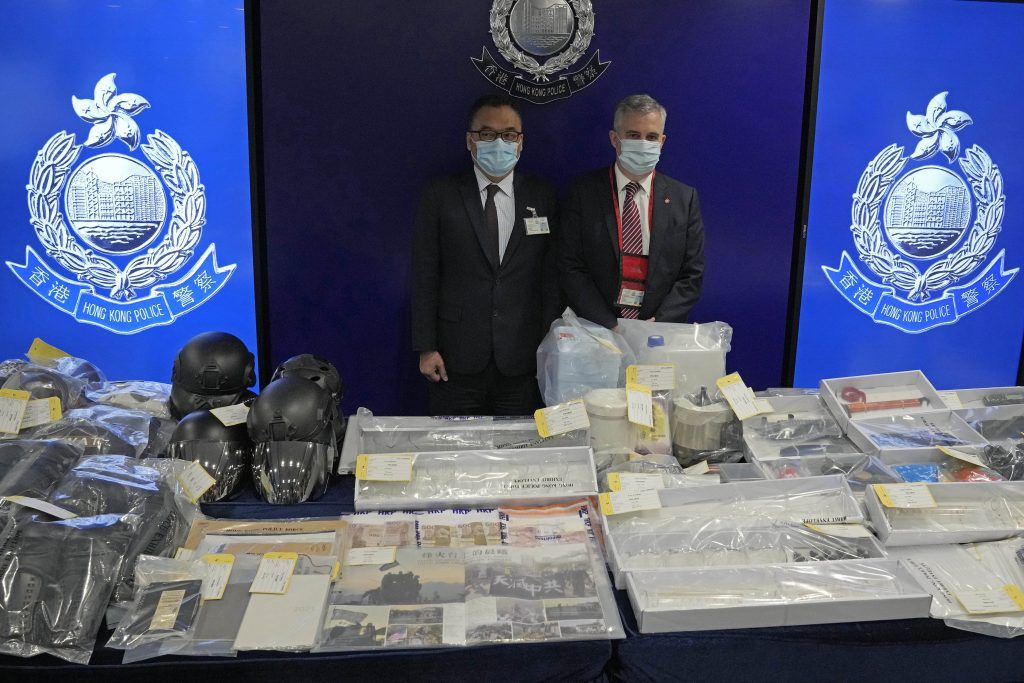 Senior Superintendent Li Kwai-wah, left, of Hong Kong Police National Security Department, and senior bomb disposal officer Alick McWhirter, right of Explosive Ordnance Disposal Bureau, pose with the confiscated evidence during a news conference as nine people were arrested over the alleged plot to plant bombs around Hong Kong, at the police headquarters in Hong Kong, Tuesday, July 6, 2021.(AP Photo/Kin Cheung).