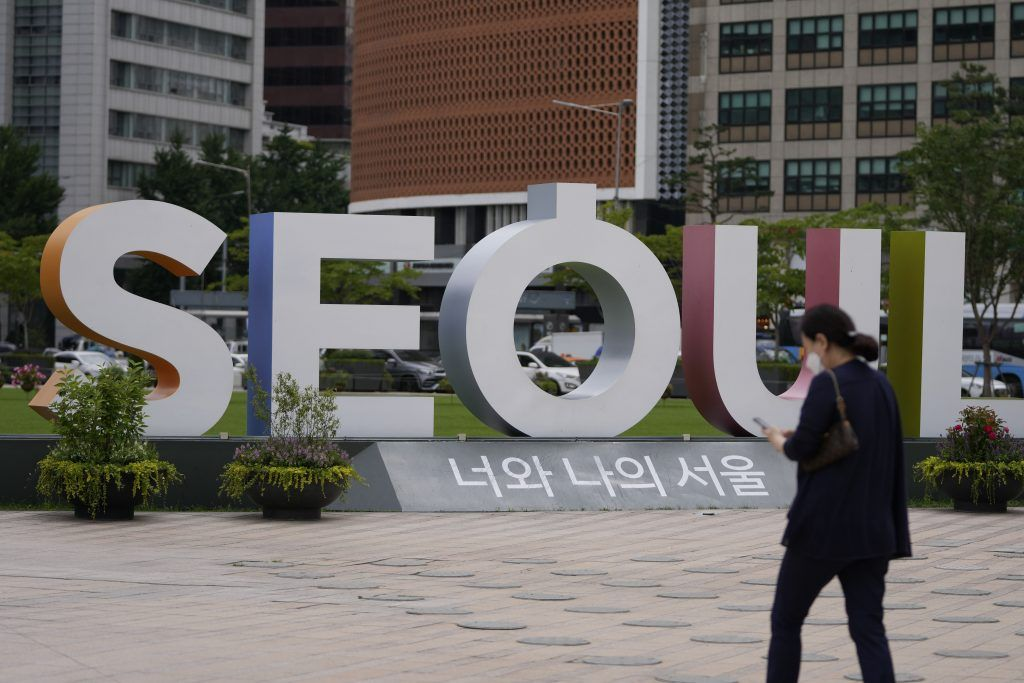 A woman wearing a face mask to help curb the spread of the coronavirus walks near the display of the Seoul logo in Seoul, South Korea, Wednesday, July 7, 2021. South Korea is seeing a steep rise in coronavirus infections unseen since the worst of its outbreak last winter as it slips into another surge while most of its people are still unvaccinated. (AP Photo/Lee Jin-man).