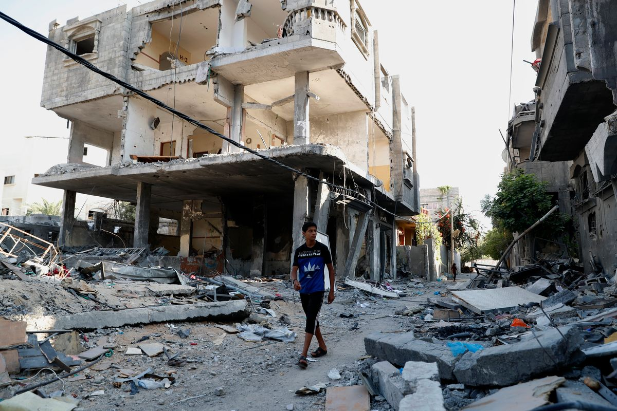 A Palestinian youth walks among the rubble of a building that collapsed after it was hit by airstrikes during an 11-day war between Gaza's Hamas rulers and Israel last May, in the Maghazi Refugee Camp, central Gaza Strip, Monday, July 12, 2021.