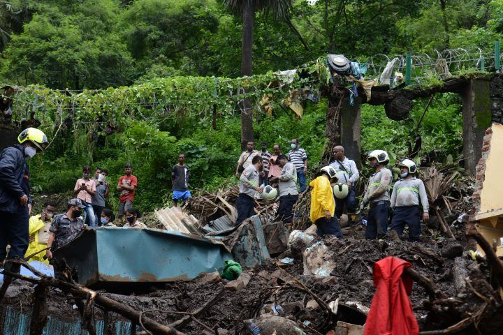 National Disaster Response Force (NDRF) and other rescue team personnel inspect the site of the landslide in a slum area where 18 people were killed after several homes were crushed by a collapsed wall and a landslide triggered by heavy monsoon rains in Mumbai on July 18, 2021.