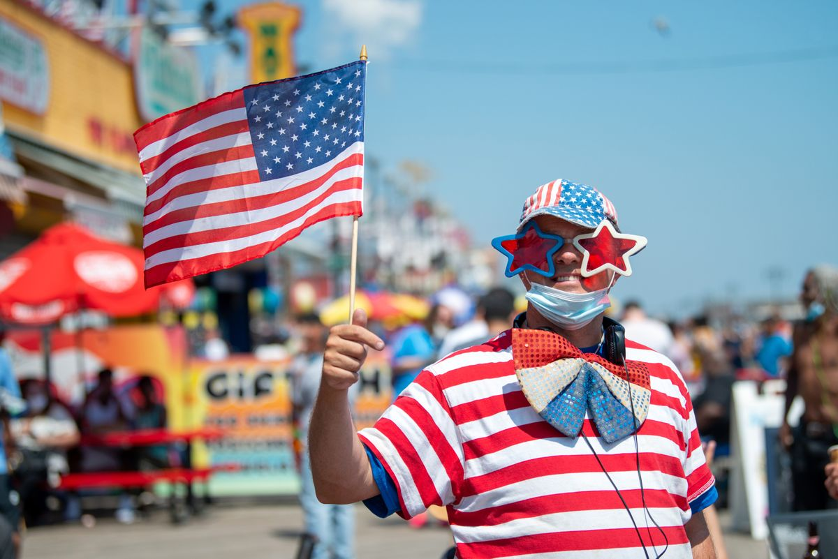 NEW YORK, NEW YORK - JULY 04: A person wearing American flag clothing poses on the boardwalk at Coney Island as the city moves into Phase 2 of re-opening following restrictions imposed to curb the coronavirus pandemic on July 4, 2020 in New York City. Phase 2 permits the reopening of offices, in-store retail, outdoor dining, barbers and beauty parlors and numerous other businesses. Phase 2 is the second of four-phased stages designated by the state. (Photo by Alexi Rosenfeld/Getty Images).