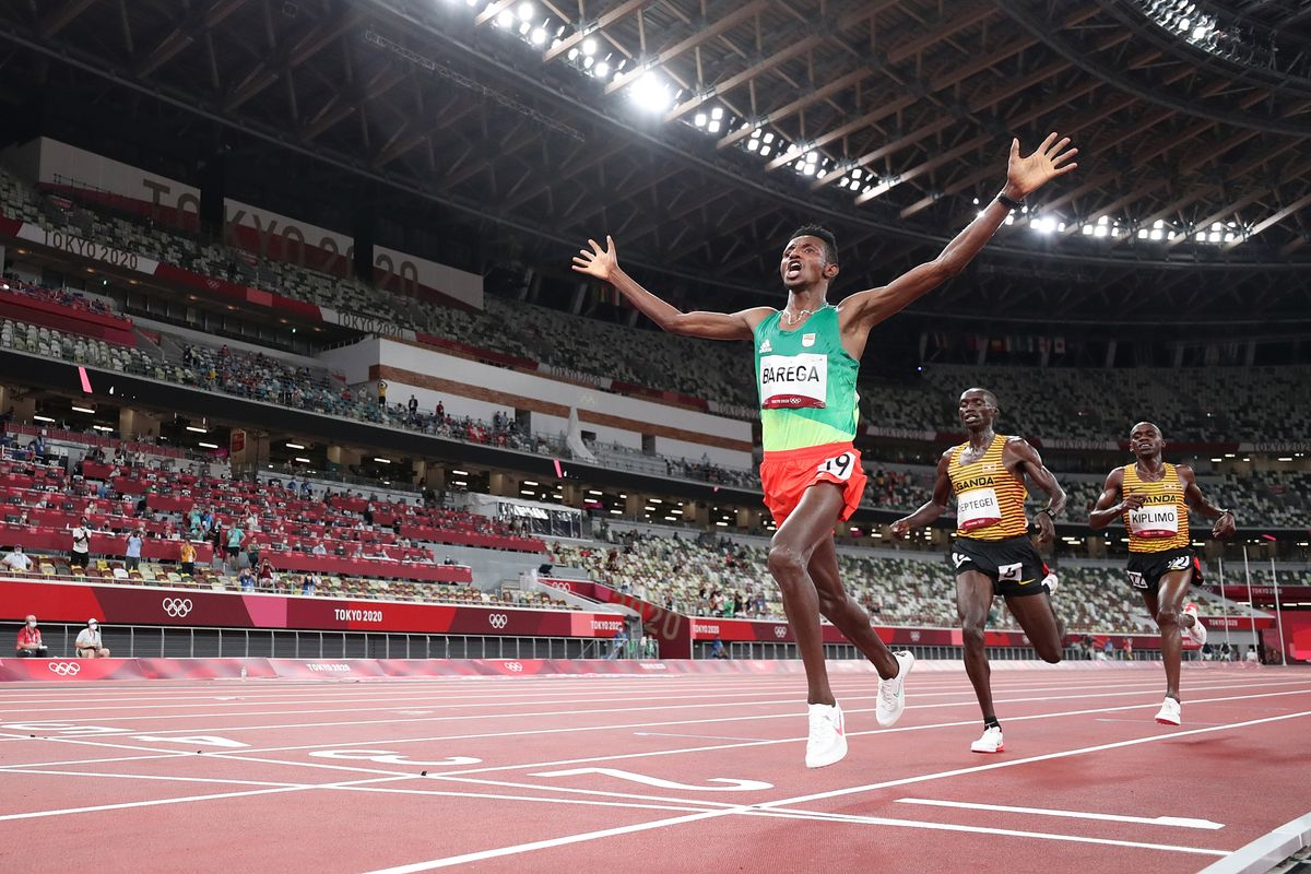 Gold medalist Selemon Barega of Team Ethiopia celebrates as he crosses the finish line ahead of silver medalist Joshua Cheptegei of Team Uganda and bronze medalist Jacob Kiplimo of Team Uganda in the Men's 10,000 metres Final on day seven of the Tokyo 2020 Olympic Games at Olympic Stadium on July 30, 2021 in Tokyo, Japan.