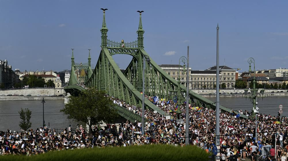 People march across the Szabadsag, or Freedom Bridge over the River Danube in downtown Budapest during a gay pride parade in Budapest, Hungary, Saturday, July 24, 2021. Rising anger over policies of Hungary's right-wing government filled the streets of the country's capital on Saturday as thousands of LGBT activists and supporters marched in the city's Pride parade.