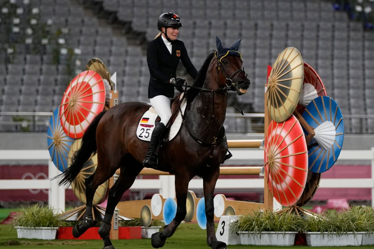 Annika Schleu of Germany cries, unable to control her horse to compete in the equestrian portion of the women's modern pentathlon at the 2020 Summer Olympics, Aug. 6, 2021, in Tokyo, Japan.