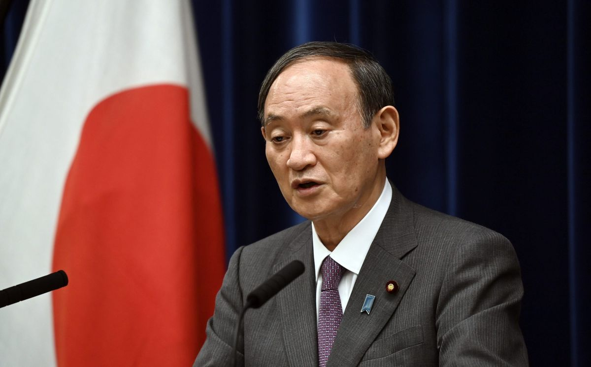 Japan's Prime Minister Yoshihide Suga attends a news conference with chairman of the government's pandemic advisory panel Shigeru Omi, not pictured, at the prime minister's official residence in Tokyo, Wednesday, Aug. 25, 2021. Japan has expanded its coronavirus state of emergency for a second week in a row, adding eight more prefectures as a surge in infections fueled by the delta variant strains the country's health care system. (Kazuhiro Nogi/Pool photo via AP).