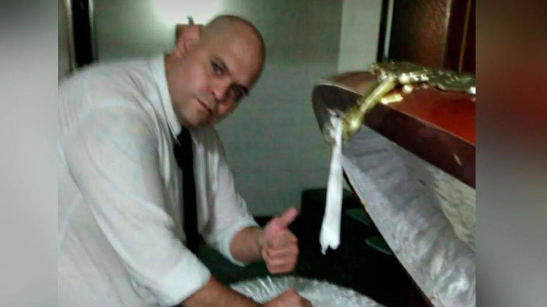 Работник похоронного бюро позирует с гробом Марадоны
