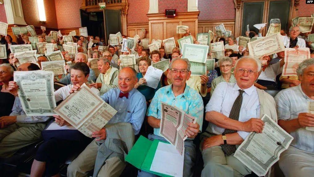 """Натовп французьких """"боржників"""" в залі суду Парижу в 2001 році демонструє російські державні облігації, придбані до більшовицької революції"""
