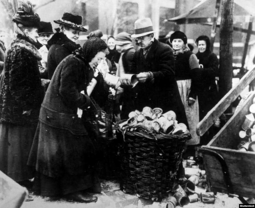 Жінка продає бляшанки на вулицях Берліна в 1923 році на тлі бідності та запаморочливої гіперінфляції