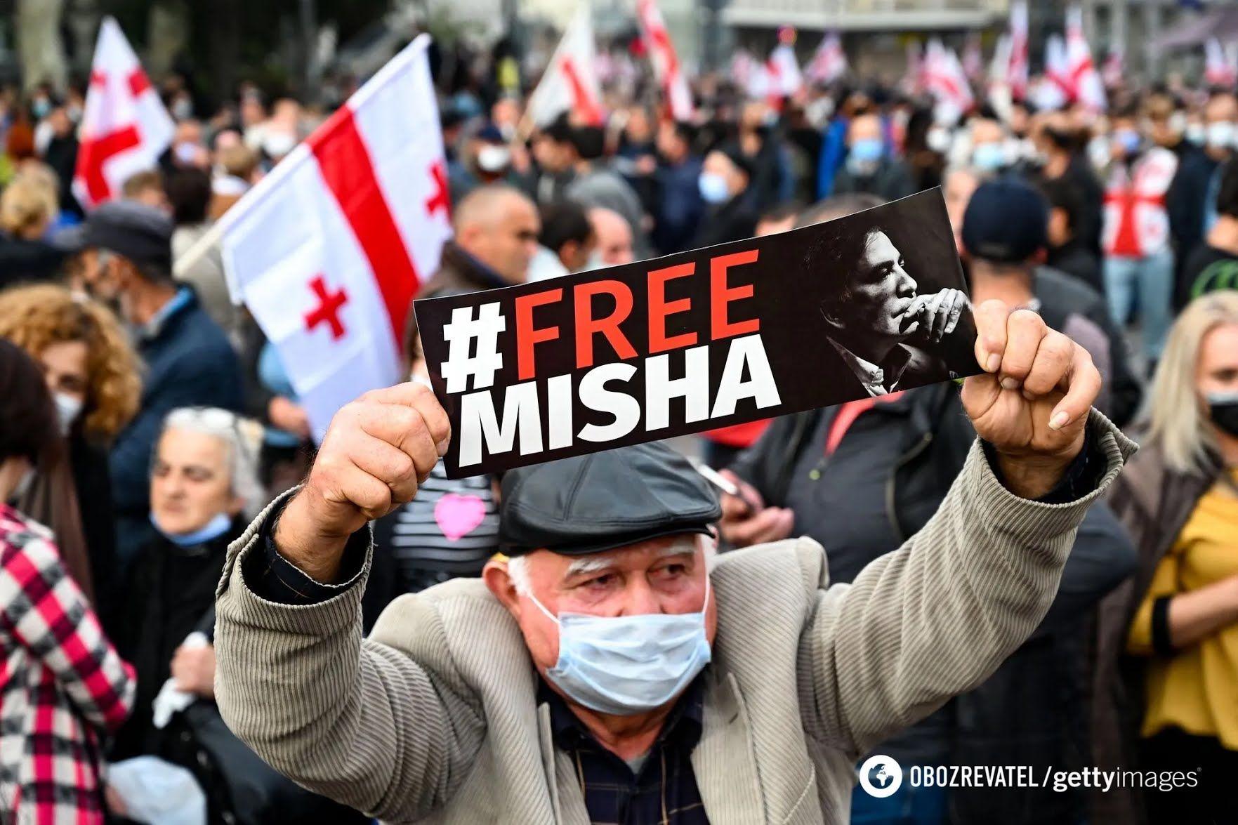 """Чоловік тримає плакат """"Свободу Міші"""""""