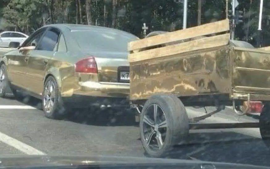 Золотий автомобіль з причепом.