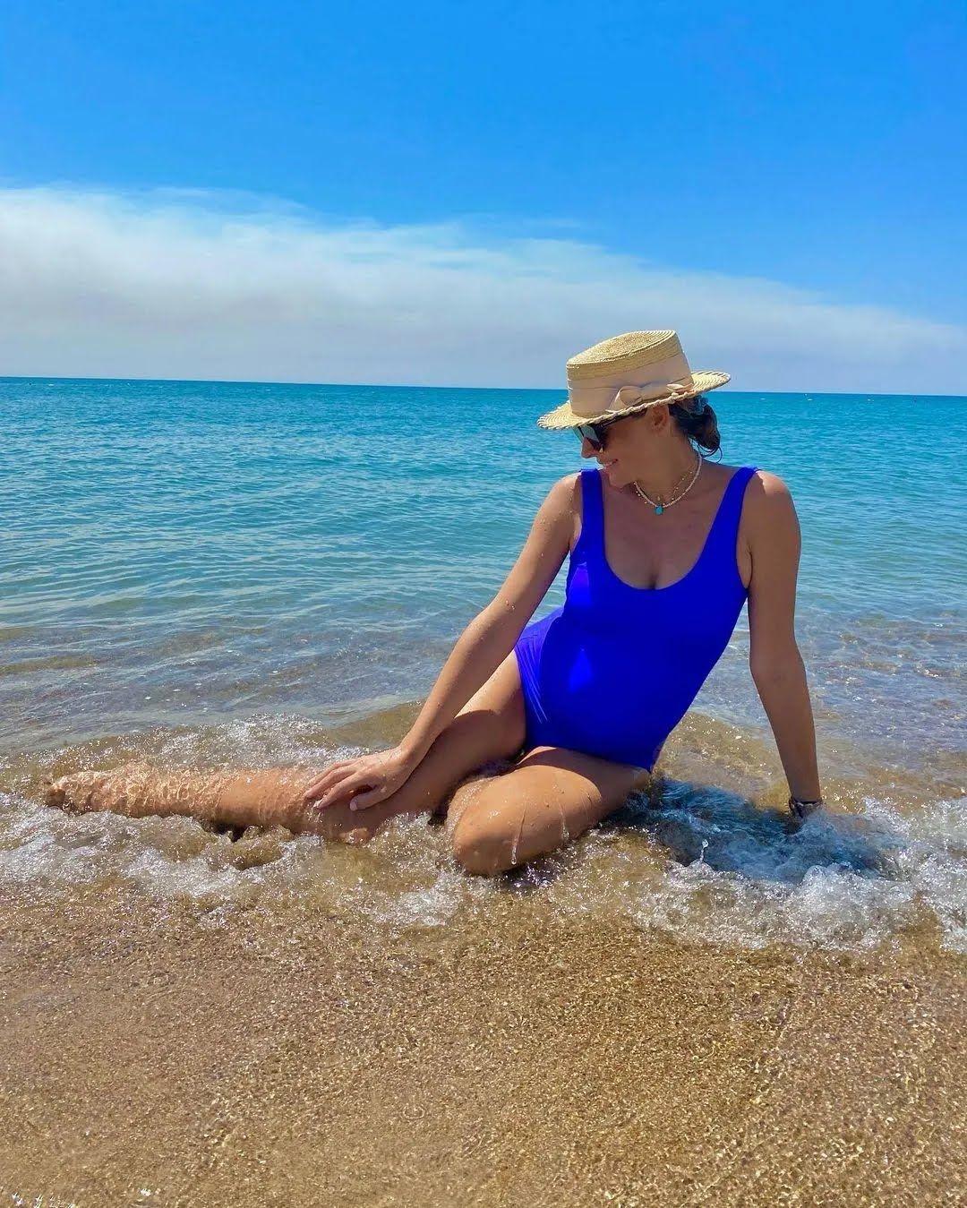 Осадча позувала сидячи на піску з видом на море