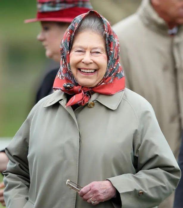Елизавета II в скромном пальто и платке на голове.