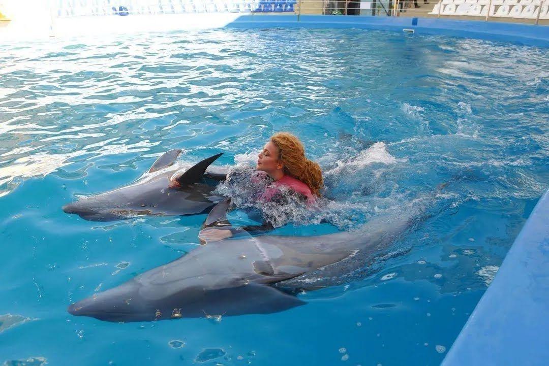Співачка плаває в басейні з дельфінами.