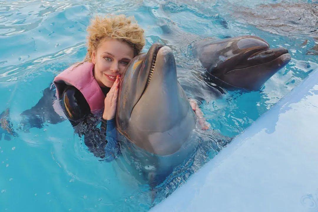 Аліна Гросу обіймається з дельфіном.