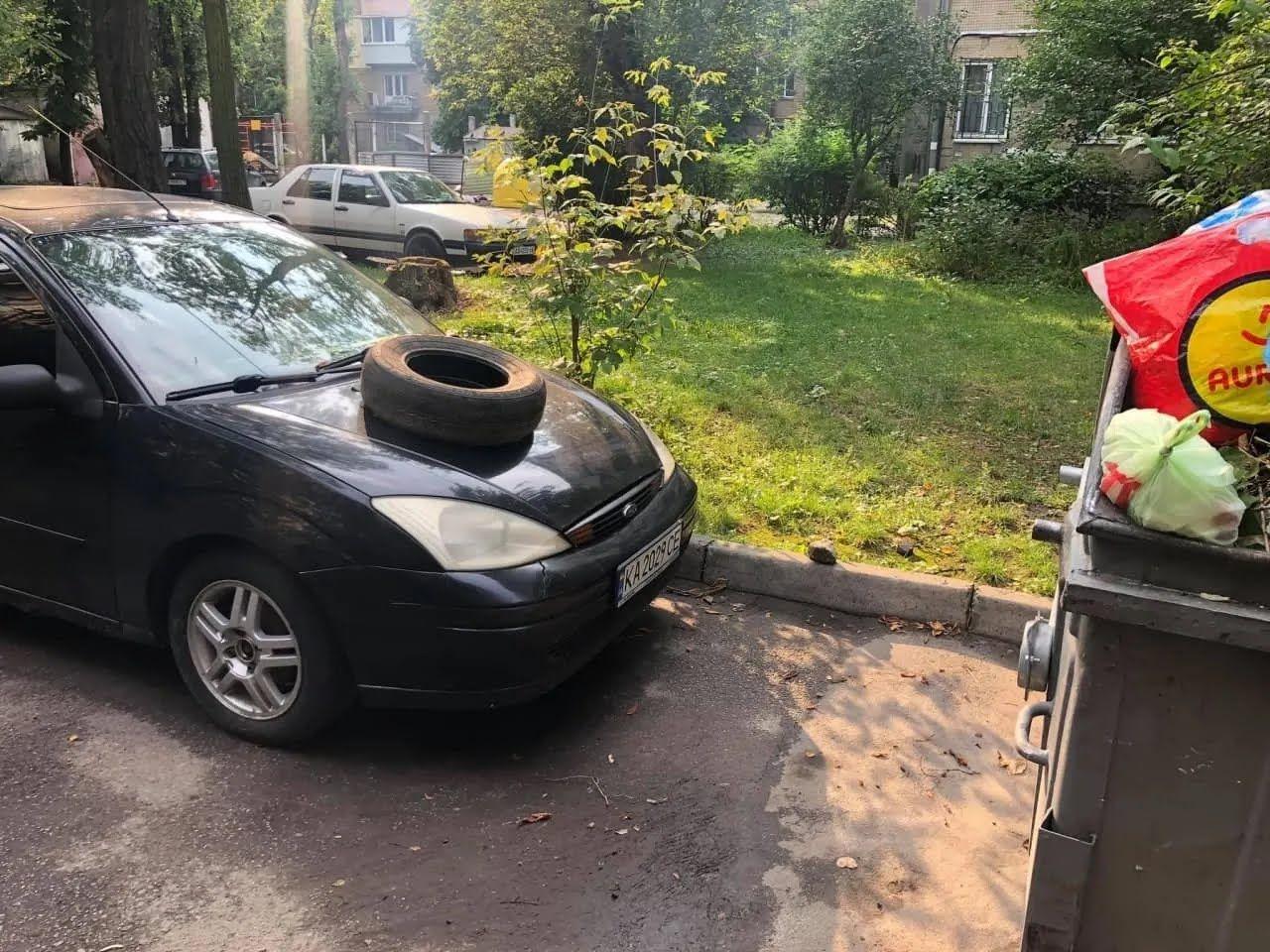 На капот авто положили автомобильную шину.