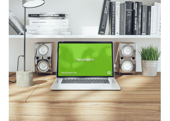 "15"" MacBook Pro on wooden table with speakers 