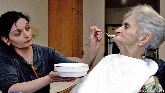 Deutschland Pflegerin füttert eine Seniorin im Altenpflegeheim
