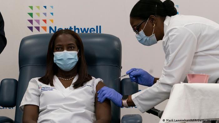 Медпрацівниця робить щеплення жінці в США