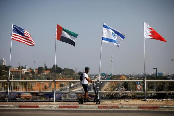 A man rides a scooter near the flags of the US, United Arab Emirates, Israel and Bahrain along a road in Netanya, Israel, September 14, 2020. [REUTERS / Nir Elias]