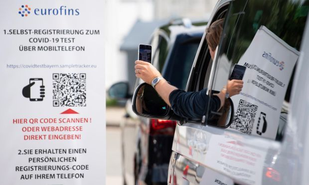 A woman scans a QR code with her smartphone at a coronavirus test centre on the motorway 93 in Germany. Photograph: Sven Hoppe/dpa/AP