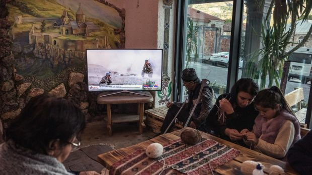 Refugees who fled the recent fighting in t Nagorno-Karabakh pass the time in a hotel lobby in Goris, Armenia. Photograph: Sergey Ponomarev/New York Times