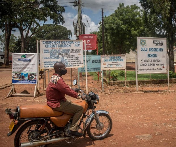 A boda boda driver rides past a sign for Gulu secondary school, which has been supported by the charity Invisible Children, producer of the Kony 2012 video