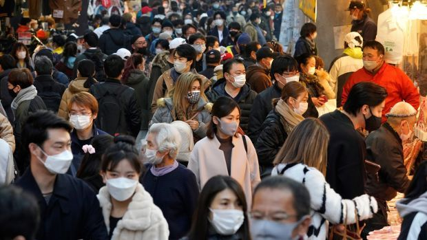 Shoppers wearing protective masks crowd the Ameyoko Street for a yearend shopping in preparation for the New Year at Ueno in Tokyo. Photograph: Kimimasa Mayama/EPA