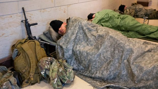 Members of the National Guard rest in the Capitol Visitor Center on Capitol Hill in Washington, on Friday after hundreds of troops were allowed to return there to rest after being forced by Capitol police to rest in a parking garage on Thursday. Photograph: Michael Reynolds/EPA