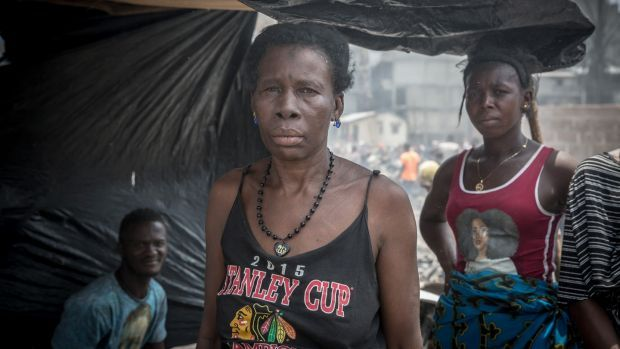 Isatu Kabia stands with her family on the site where her home used to be, in Susan's Bay, Freetown. Photograph: Sally Hayden