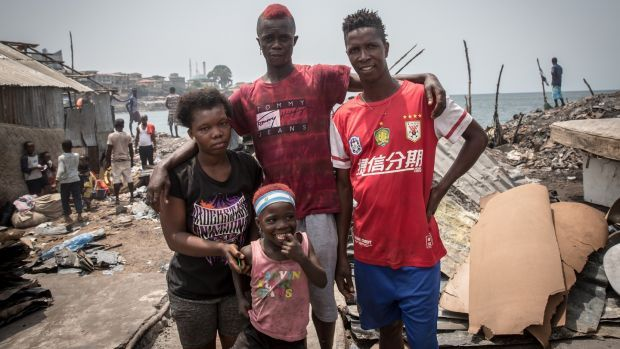 Idrissa Turay stands with his brother, wife and child on the site where their home used to be, in Susan's Bay, Freetown. Photograph: Sally Hayden