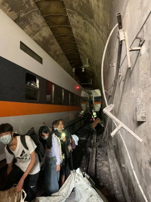 Passengers make their way out of the tunnel from the wreckage. Photograph: Handout/Central Emergency Operation Center/AFP via Getty