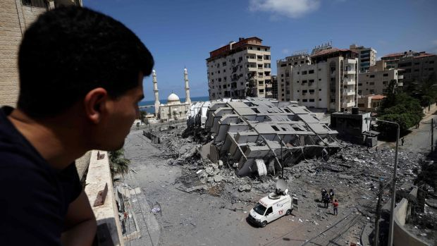 A Palestinian man looks at a destroyed building in Gaza City, following a series of Israeli airstrikes on the Hamas-controlled Gaza Strip. Photograph: Mohammed Abed/AFP/ Getty Images
