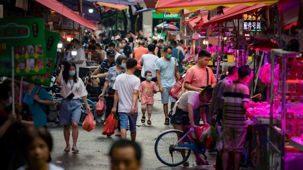 A man leads a child by the hand at a market in Guangzhou, China. Photograph: Qilai Shen/The New York Times
