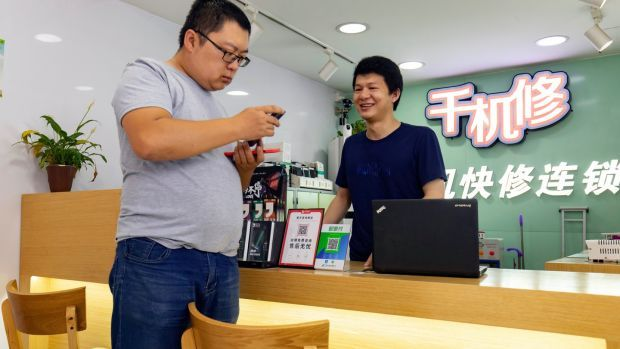 Huang Yulong assists a customer at the shop where he works repairing mobile phones in Guangzhou. Photograph: Qilai Shen/The New York Times
