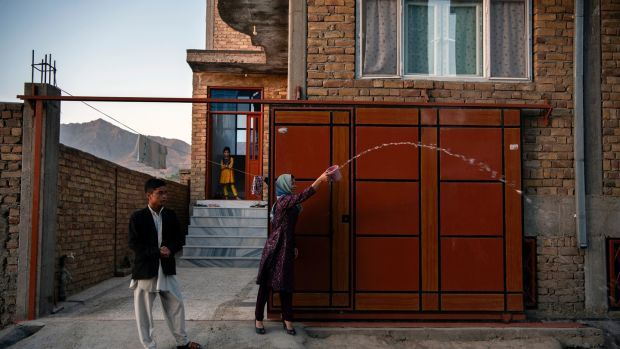 The sister and brother of Naiem Asadi throw water behind the family as they leave their house in Kabul; a tradition that is supposed to bring light to the path of a traveler and bring them home sooner on June 1st. Photograph: Kiana Hayeri/The New York Times