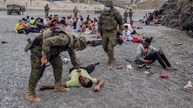 A migrant assisted by soldiers of the Spanish army near the border of Morocco and Spain, at the Spanish enclave of Ceuta, on May 18th. Photograph: Bernat Armangue/AP