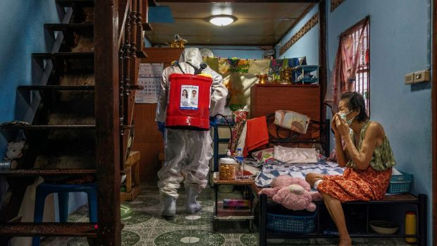 Disinfectant is sprayed in the living area of a person who tested positive for Covid-19 in Klong Toey, the largest slum in Bangkok. Photograph: Adam Dean/The New York Times