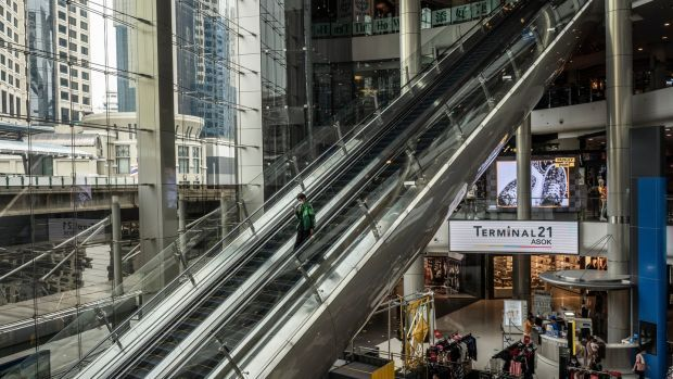 A food delivery worker rides down an escalator at a normally bustling shopping mall in Bangkok. Photograph: Adam Dean/The New York Times
