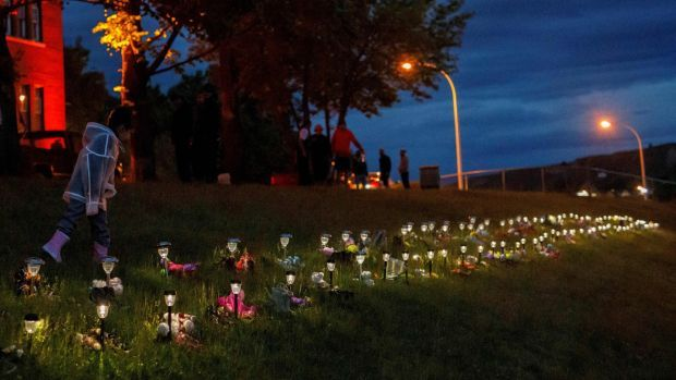 A child outside the former Kamloops Indian Residential School on June 5th after flowers and cards were left to honour the 215 children whose remains were buried in the school grounds. Photograph: Cole Burston/AFP via Getty Images