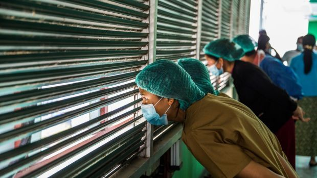 Healthcare workers in Yangon watch protesters demonstrate against Myanmar's military coup. Photograph: The New York Times
