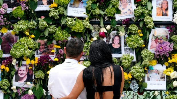 People stand near a make-shift memorial outside St Joseph Catholic Church near the Champlain Towers South residential condo on Tuesday. Photograph: AP