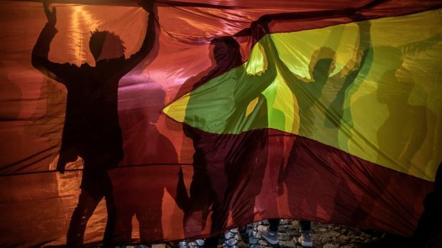 People silhouetted against the Tigrayan flag celebrate the departure of Ethiopian troops in Mekelle. Photograph: Finbarr O'Reilly/The New York Times