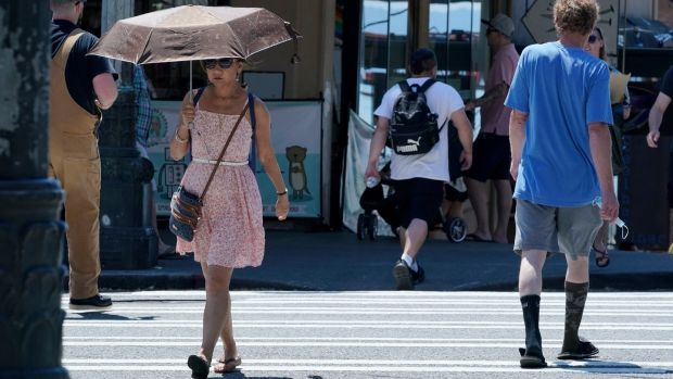 A person uses an umbrella for shade from the sun while walking near Pike Place Market in Seattle. Photograph: Ted Warren/AP
