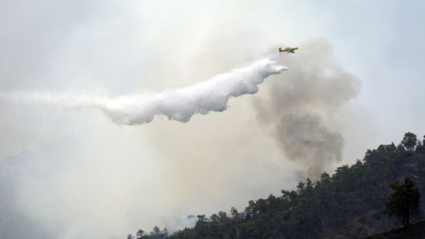 A Canadair plane flies over the forest fire in the Larnaca mountain region, Cyprus. Photograph: Katia Christodoulou/EPA