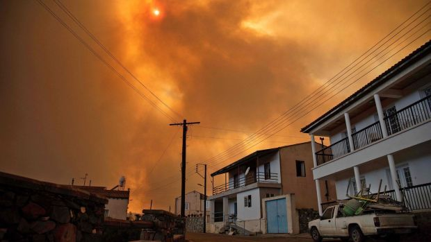 Heavy smoke covers the sky above the village of Ora in the southern slopes of the Troodos mountains, as a giant fire rages in Cyprus. Photograph: Andrea Anastasiou/AFP via Getty Images