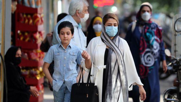 Iranians wearing face masks on a street in Tehran. Photograph: Aref Taherkenareh/EPA
