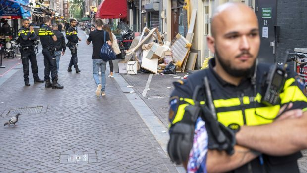 Police officers stand guard after Peter R de Vries was shot on Lange Leidsedwarsstraat in Amsterdam on Tuesday. Photograph: EPA/Evert Elzinga